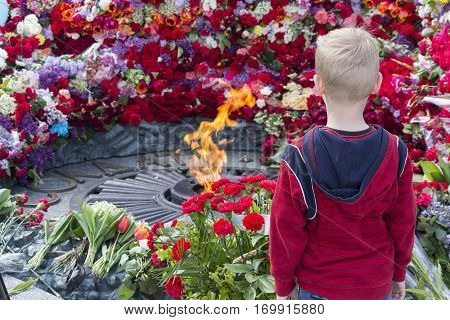 Boy at the eternal flame at the memorial of fallen soldiers of the Second World War. Kiev Ukraine