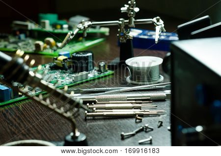 Soldering station with soft solder and tools in background