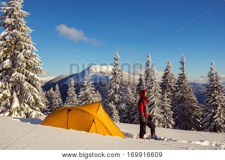 Strong Man In Snowshoes And Goggles Stands Next To A Yellow Tent
