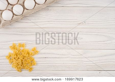 Pasta and eggs in a tray on an old white wooden table. Top view.