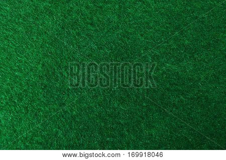 Green textured background. Green cover of poker table. Poker table close up. Green texture closeup.