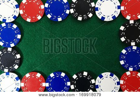 Frame of poker chips on green background. Free space for text on green textured background. Color chips on green gaming table. Game of chance concept.