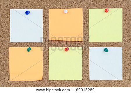 Six various and blank sticky notes on an office cork bulletin board.