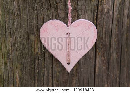 Pink wooden heart on pink sisal Cordel to the midday sun in Häselingen in February 2017, in the background a brown weathered wooden wall.