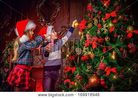 Merry Christmas and Happy New Year. Two happy children decorate Christmas tree with toys. Beautiful living room with fireplace decorated for Christmas.