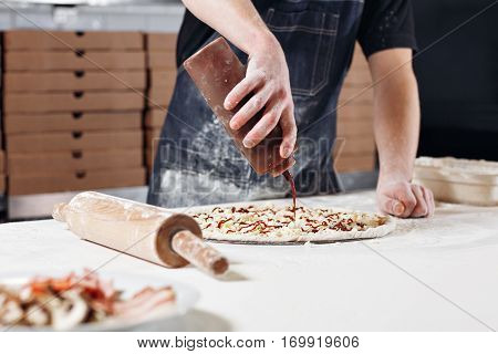 Cooking pizza. the workpiece poured tomato sauce. Closeup hand of chef baker in uniform blue apron cook at kitchen.