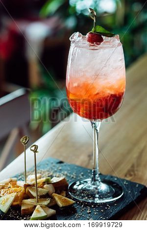 Sangria with apples, oranges and strawberries on wood