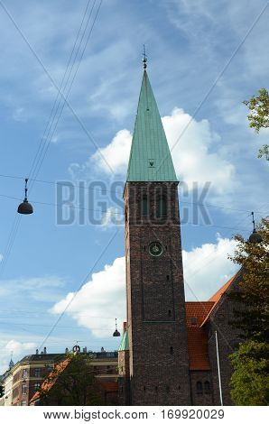 An exterior view of a tall church spire in Copenhagen