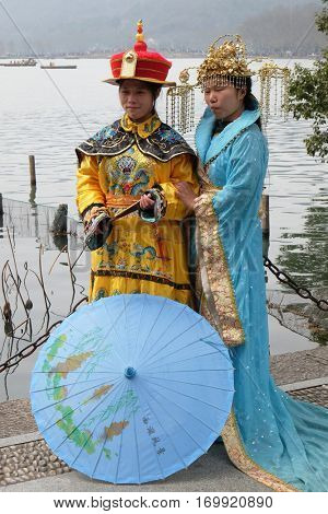 HANGZHOU - FEBRUARY 21: Two girls posing in traditional Chinese costumes on the shores of West Lake (Xi hu lake) in Hangzhou, China, February 21, 2016.
