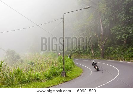 Heavy fog on the road bad weather for driving motorbike. Road through misty evergreen jungle forest. Winter rainy season. Indonesia.