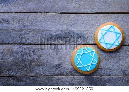 Tasty glazed cookies for Hanukkah on wooden table