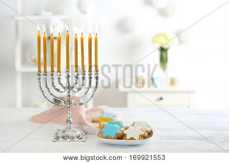 Beautiful composition for Hanukkah on wooden table against blurred background