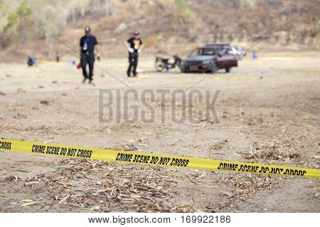 police line tape and blurred law enforcement and wrecked car background with copy space