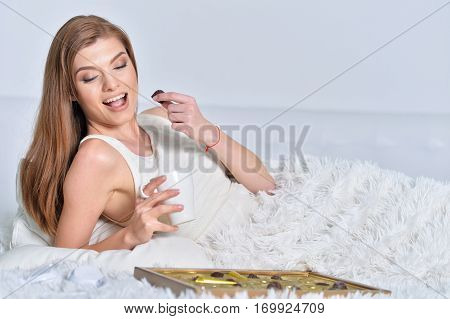 young beautiful woman eating chocolate in bed