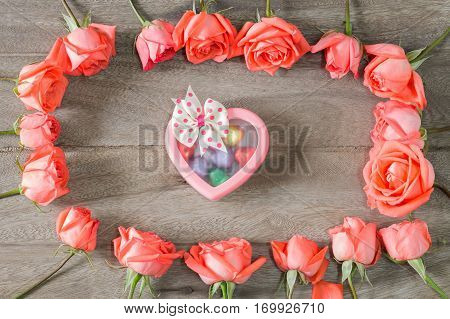 Romantic floral frame background. Valentines day background.Pink roses on wooden background