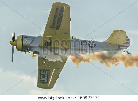 BUCHAREST ROMANIA - OCTOBER 4 2014: Aerobatic airplane pilots training in the sky of the city. Colored airplane with trace smoke.