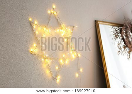 Star of David made from garland on wall. Hanukkah concept