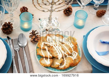 Plate with tasty potato pancakes on table served for Hanukkah