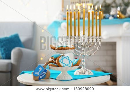 Menorah, dreidels and cookies for Hanukkah on stool in living room, closeup