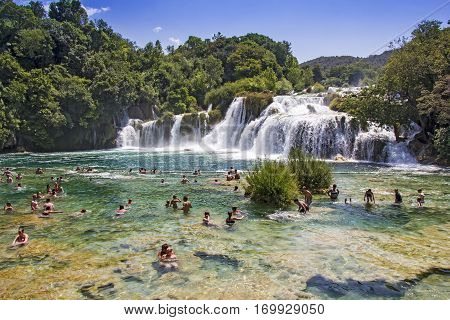 KRKA NATIONAL PARK CROATIA - JULY 10 2016: Many tourists swim in the Krka River in the Krka National Park in Croatia. This is one of the most famous national parks in the country which in the season is visited by many tourists from around the world.