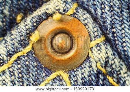 Metal button on blue jeans high magnification macro image