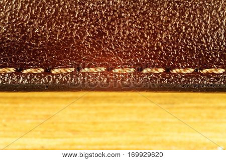 Stitched brown leather texture on wooden background close up view
