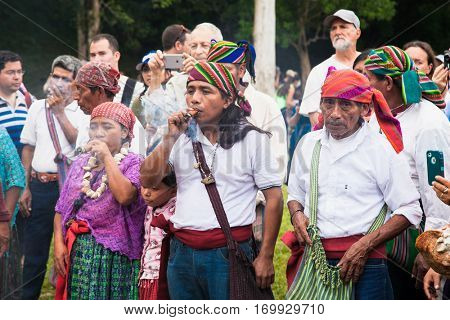 TIKAL, GUATEMALA - DEC 21, 2015: Unidentified Mayan people and tourists surround a fire on December 21, 2015  in Tikal, Guatemala. Traditional Mayan fire ceremony at the 2015 new year celebrations.