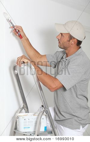 Man painting walls in white