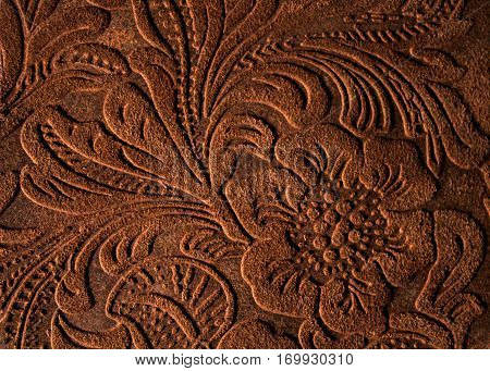 Brown leather background with floral design emboss.