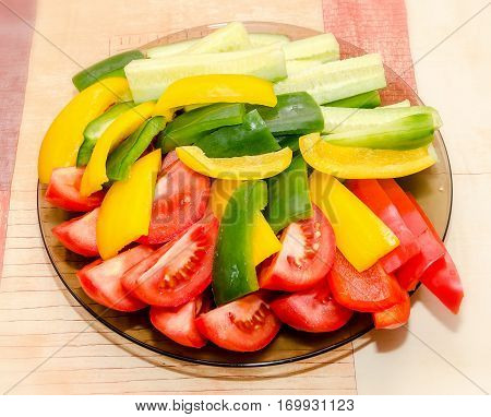 Transparent Plate With Sliced Red Tomatoes, Yellow And Green Capsicums And Cucumbers