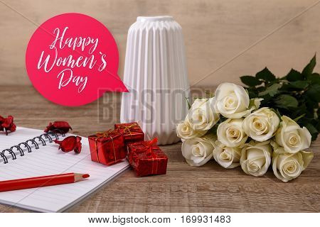 White roses with gift boxes and vase. Happy Womens day, 8 march concept. Red pencil with notebook and candle. Love design. Wooden rustic board.