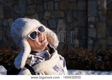 Funny little girl in sunglasses in winter a sunny day. Caucasian stylish little girl in winter clothes walking outdoor. Pretty charming little girl. Portrait of little fashion kid girl .