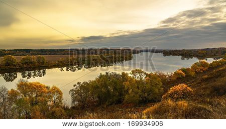 autum River with banks covered with forest in autumn on a cloudy day