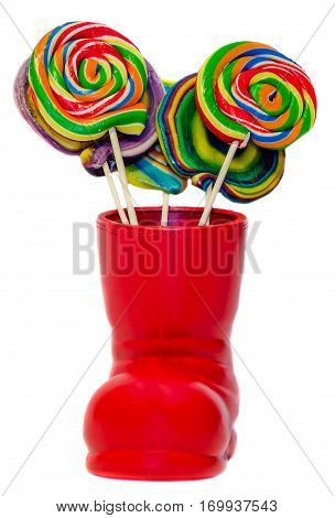 Santa Claus red boots shoes with colored sweet lollipops candys. Saint Nicholas boots with presents gifts