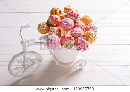 Bright cake pops in decorative bicycle on white wooden background. Selective focus.