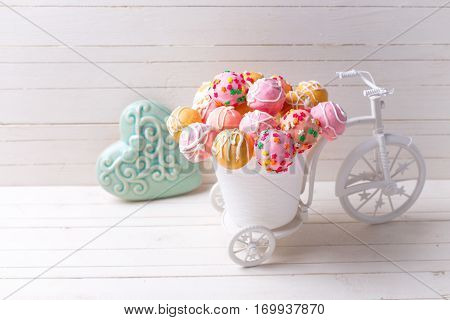 Colorful cake pops in decorative bicycle and turquoise heart on white wooden background. Selective focus. Place for text.