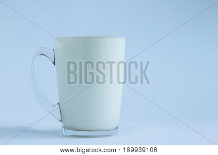 Full transparent glass poured milk on light white and blue background