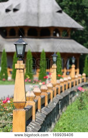 A wooden fence with a traditional Romanian Maramures wooden house in the background.