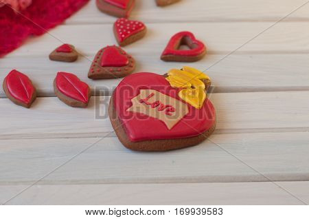 Several red glazed honey cakes in shape of heart lips lay on white wooden background