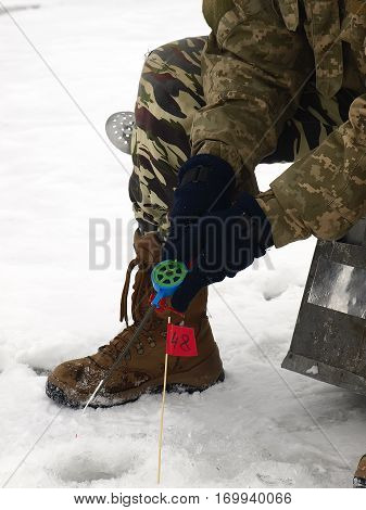 Ice fishing competition. competitor catches the fish on Ice Fishing