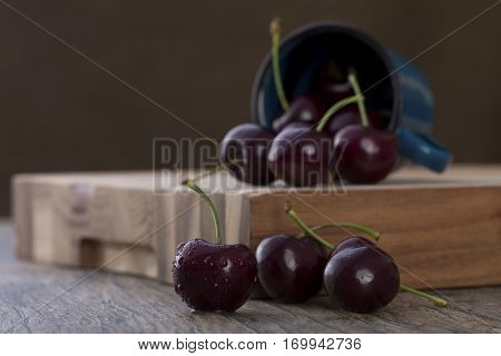 Close-up of cherries in a blue cup on brown wood background