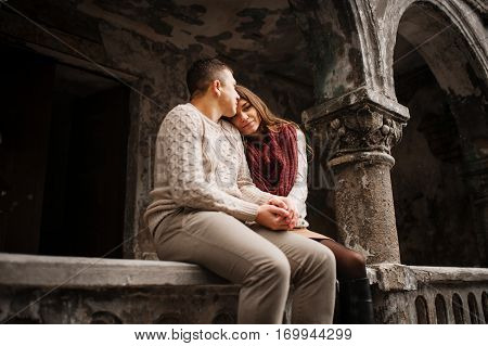 Young Couple Wearing On Tied Warm Sweaters In Love Sitting On Stone Baluster At Old Yard With Arch A