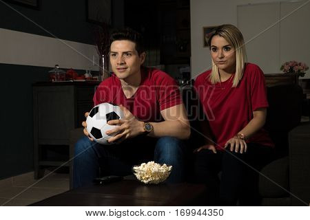 Couple Watching A Soccer Game In The Dark