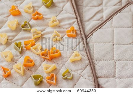 Colored Italian pasta in hearts shape on the kitchen textiles. Food background. Italian tricolor pasta in the shape of hearts. Mediterranean food