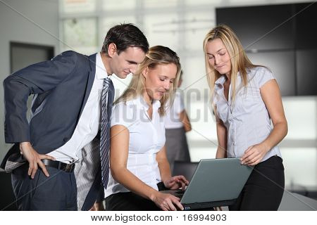 Co-workers with laptop computer in the office