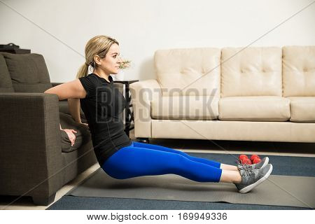 Woman Doing Tricep Dips On A Couch At Home