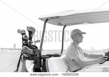 Middle-aged man driving golf cart at course