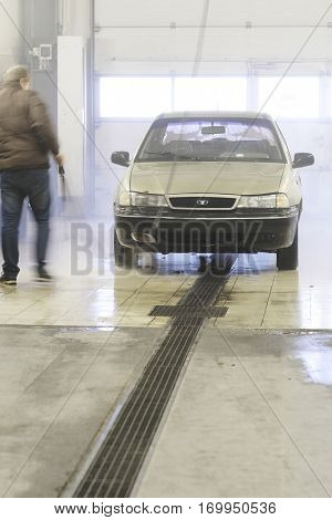 Moscow, Russia, December, 15, 2016: Servicemen (he is blurred) washes an automobile in a car wash