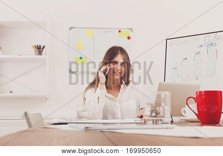 Beautiful young businesswoman talking, answer a call at mobile phone, sitting at wooden desk with laptop and red cup. Modern office worker in white room. Succesfull woman, female carreer concept.