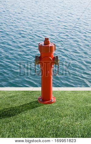 Plenty of water concept image. Fire extinguisher on a harbor pier with copy space